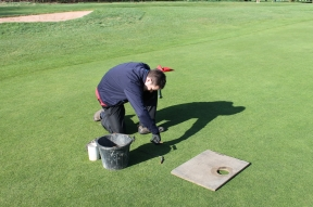 Greenkeeper cutting a hole