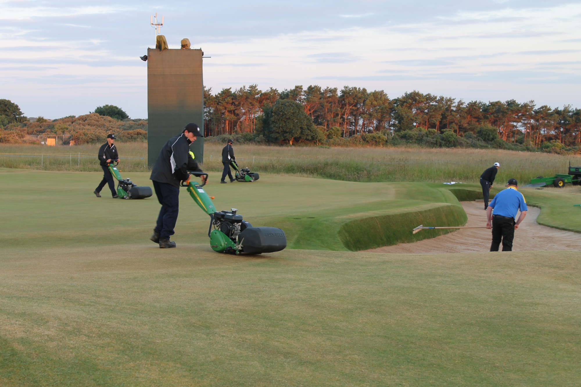 Greenkeepers mowing green and sweeping bunkers